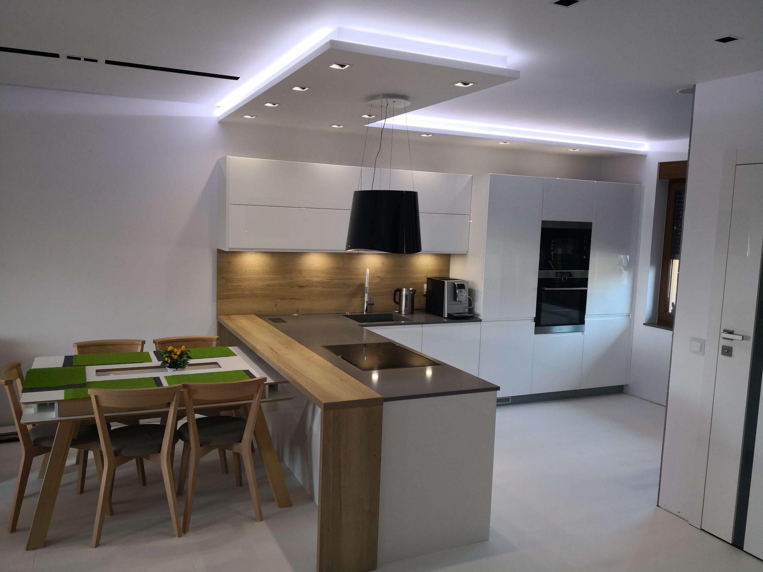 Białe meble kuchenne na wysoki połysk z akcentem jasnego drewna